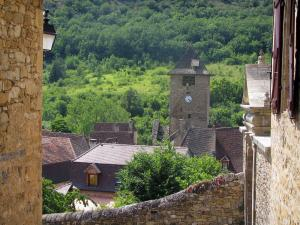 Autoire - Church bell tower, houses of the village and trees, in the Quercy