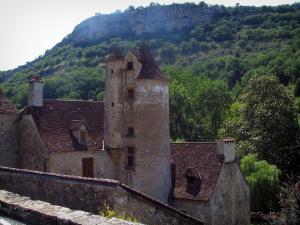 Autoire - Limargue castle with its tower and its corbelled turret, trees and cliff, in the Quercy