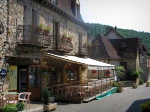 Autoire - Restaurant terrace, street and houses of the village, in the Quercy
