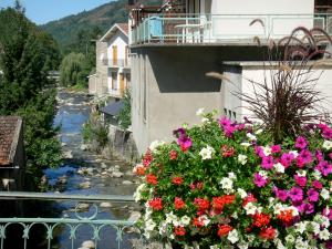 Ax-les-Thermes - Spa town: flower-decked bridge spanning the river, houses and trees along the water