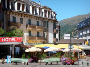 Ax-les-Thermes - Spa town: building facades, restaurant terrace shaded by umbrellas, benches and flowers