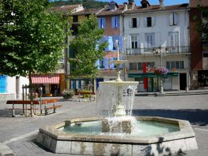 Ax-les-Thermes - Spa town: Fountain of the Place Roussel square, trees, benches and facades of houses
