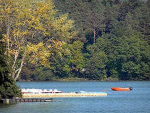 Aydat lake - Lake, pontoon, boats, paddle boats and trees lining the water; in the Auvergne Volcanic Regional Nature Park