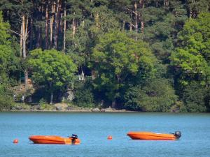 Aydat lake - Two small boats on the lake and trees along the water; in the Auvergne Volcanic Regional Nature Park