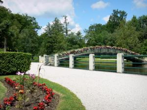 Bagnoles-de-l'Orne - Flowerbed and walk in the foreground with a view of the flower-bedecked bridge spanning the lake
