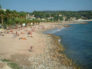 Bandol - Palm trees, sandy beach of the seaside resort with tourists, pebbles, the Mediterranean Sea, houses and forest in background