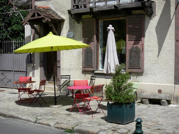 Barbizon - Facade of a house and sidewalk decorated with bushes in pots, tables, chairs and a parasol