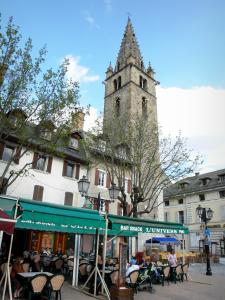 Barcelonnette - Cardinalis tower (Clock tower) overlooking the Manuel square (houses, café terrace, lampposts and trees)