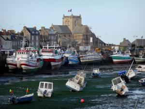 Barfleur - Port: small leisure boats at ebb tide, fishing boats moored to the quay, granite houses and church of the village, in the Cotentin peninsula