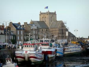Barfleur - Port: fishing boats moored to the quay, granite houses and church of the village, in the Cotentin peninsula