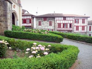 La Bastide-Clairence - Flower beds in the garden of the church and houses with red shutters of the Navarre fortified town