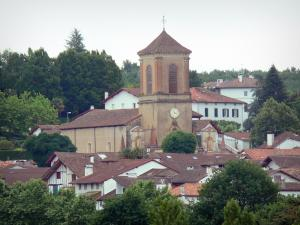 La Bastide-Clairence - View of the bell tower of the Notre-Dame de l'Assomption church and the roofs of houses of the Navarre fortified town surrounded by greenery