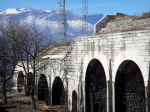 Bastille fort - Bastille (in the town of Grenoble): casemates of the fort, trees, benches and mountains in the background