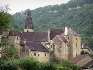 Baume-les-Messieurs - Abbey with its abbatial buildings and bell tower of the Saint-Pierre abbey church, trees