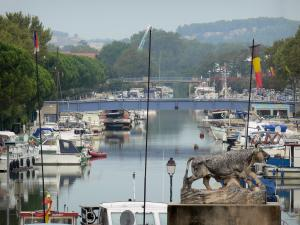 Beaucaire - Port with boats moored to the quays, Rhône canal in Sète, flags, statue of a bull and trees