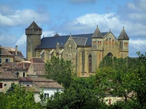 Beaumont-du-Périgord - Fortified church of Gothic style, houses of the fortified town, trees and cloudy sky