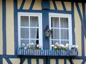 Le Bec-Hellouin - Flower-bedecked window of a blue half-timbered house