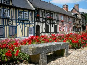 Le Bec-Hellouin - Facades of half-timbered houses, blooming roses, and bench