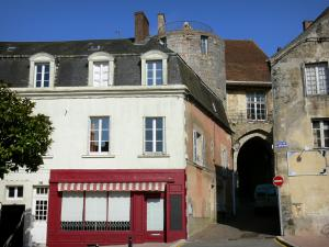 Bellême - Facades of houses of the Place de la République square and porch (remains of old walls) in the background; in the Perche Regional Nature Park