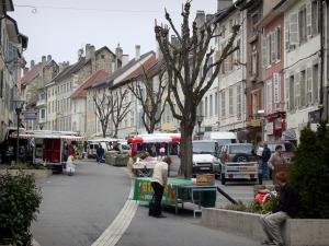 Belley - Stalls of the Saturday morning market, trees and facades of houses in the old town