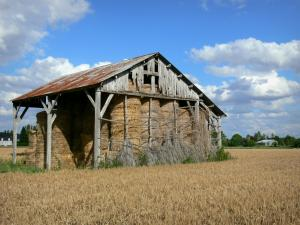 Berry landscapes - Hay barn in the middle of a field; clouds in the blue sky