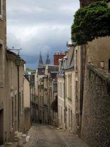 Blois - Sloping narrow street lined with houses, lampposts and turbulent sky