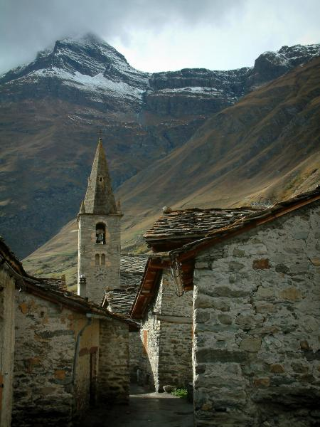 Bonneval-sur-Arc - Old stone houses with slate roofs, church bell tower in the Savoyard village, and mountain with snowy summit, in Haute-Maurienne (Vanoise national park)