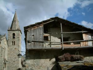 Bonneval-sur-Arc - Ancient stone house with its wooden balcony, church bell tower in the Savoyard village and cloudy sky, in Haute-Maurienne (Vanoise national park)