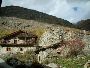 Bonneval-sur-Arc - Ruins, stone house with a wooden balcony and a mountain, in Haute-Maurienne (Vanoise national park)