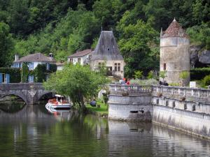 Brantôme - Dronne river, bridge Coudé in background, pavilion of the Renaissance period, Saint-Roch tower, houses and trees, in Green Périgord