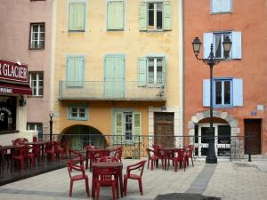 Briançon - Upper town (Vauban citadel, fortified town built by Vauban): Place d'Armes square with a café terrace and a lamppost, colourful facades of the old town