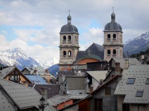 Briançon - Upper town (Vauban citadel, fortified town built by Vauban): bell towers of the Notre-Dame collegiate church and roofs of houses of the old town, view of the mountains with snowy tops (snow)