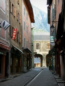 Briançon - Upper town (Vauban citadel, fortified town built by Vauban): Grande Rue high street (Grande Gargouille) with its central channel, its houses and its shops, Pignerol door and guardroom in background