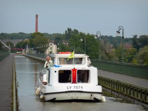 Briare aqueduct - Boat navigating on the aqueduct waterway, towpaths and lampposts, trees and houses in background
