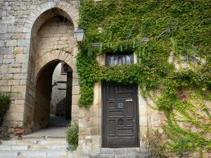 Bruniquel - Porte Méjane gate and facade of a house covered with Virginia creeper