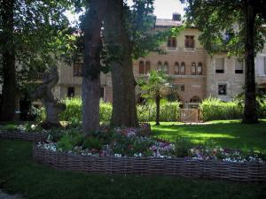 Cahors - Olivier-de-Magny public garden (flowers, lawns and trees) and houses of the Daurade street, in the Quercy