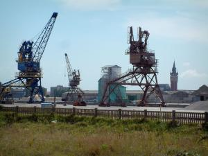 Calais - Grassland, cranes on a shipyard and a belfry in background