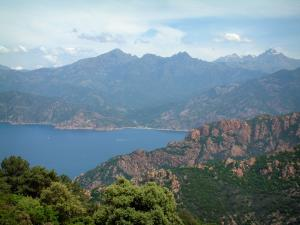 Calanche de Piana creeks - Red granite cliff (creeks), the Mediterranean sea and mountains with some snowed peaks
