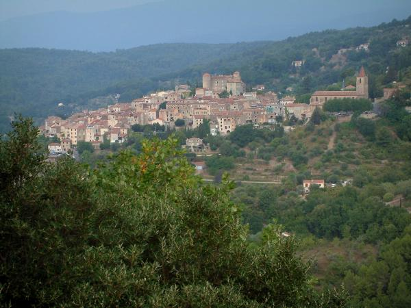 Callian - Trees in foreground, forest, church, castle and houses of the hilltop village