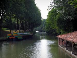 Canal du Midi - Canal with a barge and trees along the water