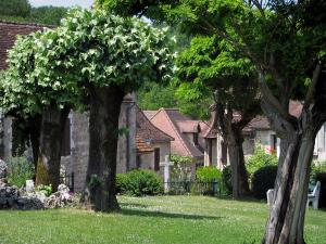 Carennac - Public garden featuring trees with view of the stone houses of the village, in the Quercy