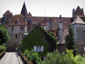 Carennac - Flower-covered bridge, houses of the village, bell tower of the Saint Pierre church, former priory and Doyens castle (on the left), in the Quercy