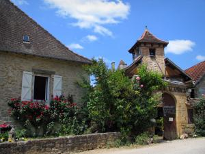 Carennac - Entrance to the Alambics museum, shrubs and houses of the village, in the Quercy