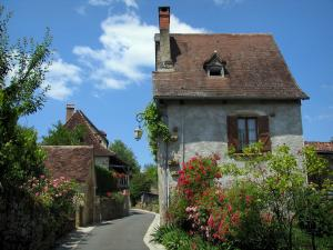 Carennac - Street decorated with flowers, flower-bedecked rosebushes and houses, in the Quercy