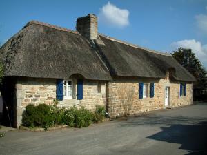 casas con tejado de paja casa de piedra con techo de paja con persianas azules