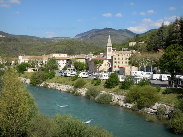Castellane - Verdon river, bell tower of the Saint-Victor church, houses of the old town and mountains; in the Verdon Regional Nature Park