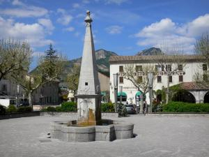 Castellane - Fountain, trees and houses of the Marcel Sauvaire square; clouds in the blue sky