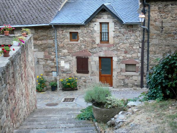 Castelnau-Pégayrols - Facade of a stone house and flowers in the medieval village