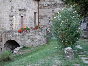 Castelnau-Pégayrols - Old Saint-Michel priory, geraniums in pots and shrubs in bloom