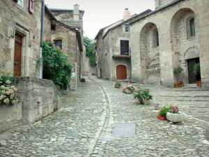 Castelnau-Pégayrols - Paved street, Saint-Michel church, stone houses and floral decorations in the medieval village